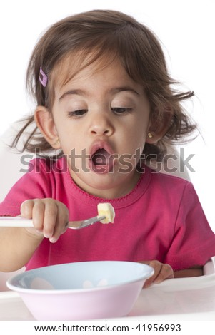 Baby girl is eating by herself - stock photo