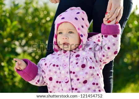 baby girl showing something with finger to her mother