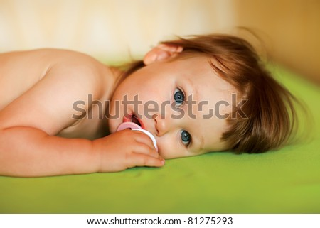 Baby girl with a soother in her mouth - stock photo
