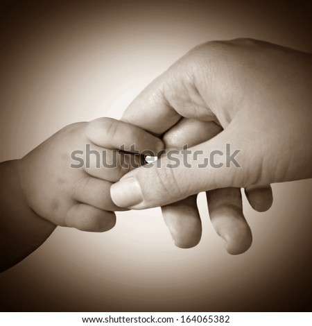 Baby hand gently holding mother's finger, sepia style - stock photo