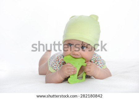 baby lying down on white blanket playing with green toy studio shot isolated on white caucasian - stock photo