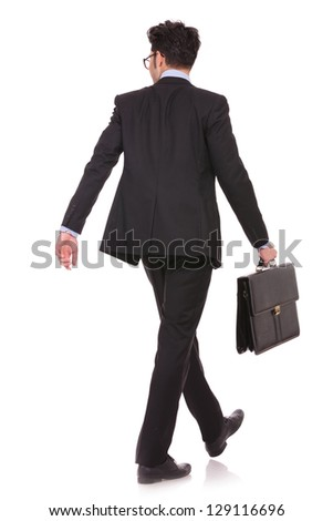 back view full length picture of a young business man walking with his suitcase and looking at something in a side direction on white background - stock photo