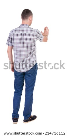 back view of man. Young man jeans presses down on something. Isolated over white background. Rear view people collection. backside view of person. she holds his hand open, palm forward - stock photo