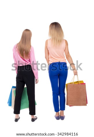 back view of  two women  with shopping bags. backside view of person.  Rear view people collection. Isolated over white background. Two girls with paper handles are close and look ahead. - stock photo