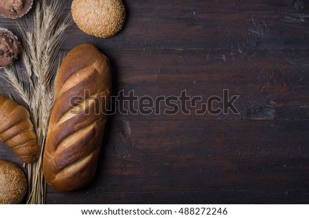 baked bread and wheat on wooden background.