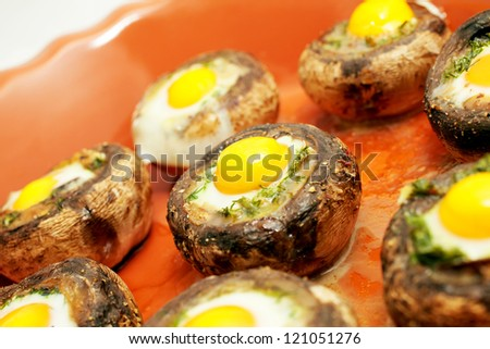 Baked mushrooms with quail`s eggs - stock photo