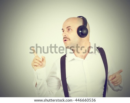 bald man with a mustache businessman listening to music on headphones and sings - stock photo