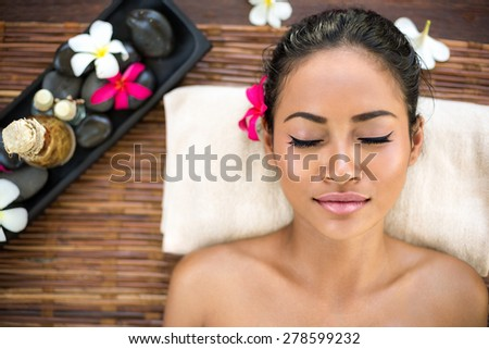 Balinese woman relaxing in spa salon smiling relaxing with eyes closed - stock photo