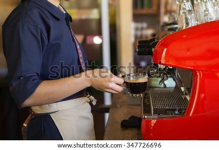 Barista coffee making black coffee by coffee making machine - stock photo