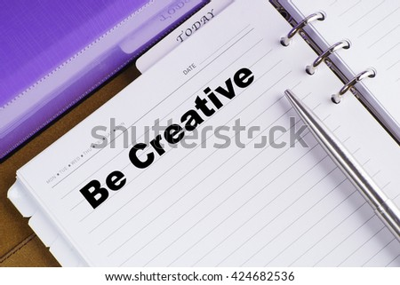 """Be Creative"" text on notebook on a wooden table with open diary and pen - conceptual images"