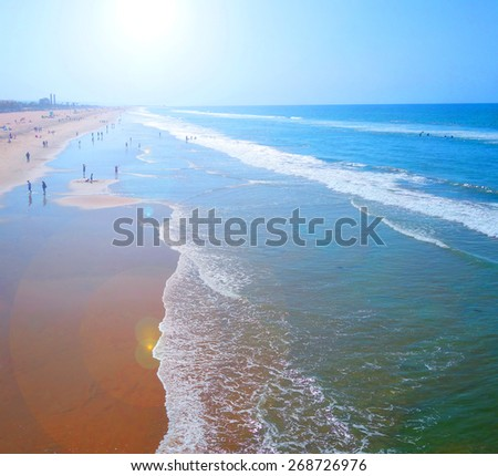 beach with sand and waves and bright sun flare                               - stock photo