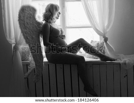 Beautiful angelic pregnant woman. Angel black white photo - stock photo
