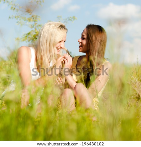 2 beautiful blond & brunette young women teen girl friends having fun laughing on spring or summer green nature & blue sky outdoors background portrait image