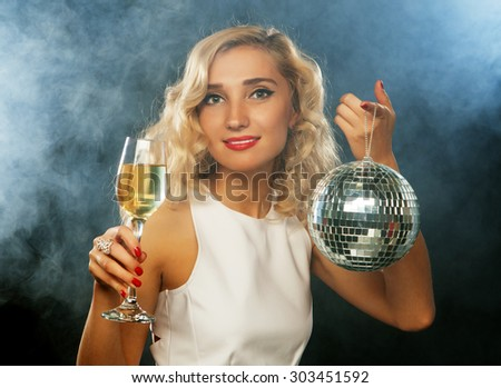 beautiful blond woman in evening dress with wine and disco ball - stock photo
