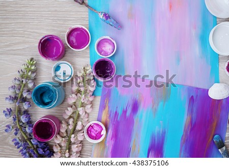 Beautiful composition of art process,paintings and paints around,violet and blue colors on the wooden background - stock photo