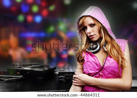 Beautiful DJ girl in pink standing in the front of the decks - stock photo