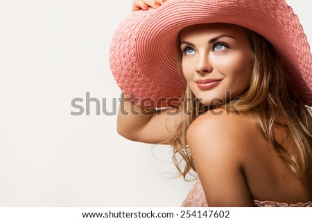 Beautiful girl . A tanned slim girl in a hat with a light-up. Cute woman in a peach hat on her head,her face a gentle make-up and a beautiful smile.Portrait of a girl in the hat on a light background - stock photo