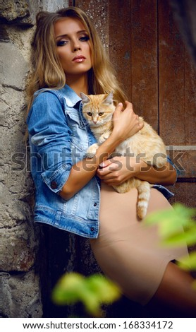 beautiful girl with blond hair with cat                       - stock photo