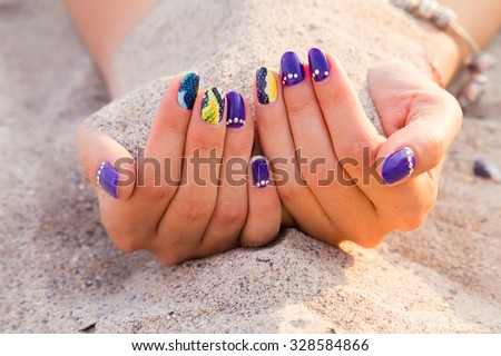 Beautiful hands with a professional manicure on the sand. Bright and beautiful manicure. Macro shooting hand. Photo for fashion magazines, websites and backgrounds.  - stock photo