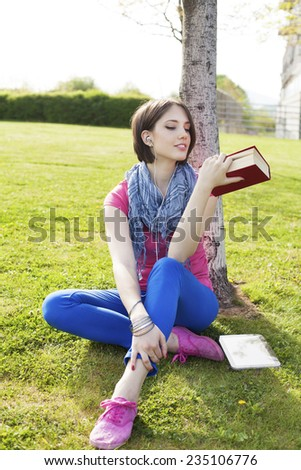 Beautiful happy young woman sitting on grass, enjoy sunny day and listening music with headphones while reading book, chilling.  - stock photo