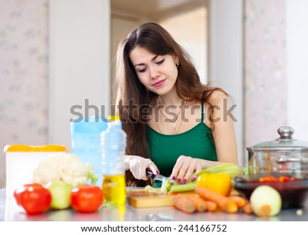 beautiful housewife cutting vegetables in her kitchen at home  - stock photo