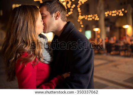 Beautiful pretty girl kissing handsome boy on street with Christmas light in background