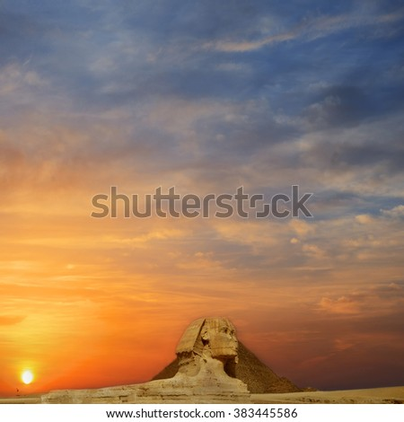 Beautiful profile of the Great Sphinx including pyramids of Menkaure and Khafre in the background on  sunset, blue sky day in Giza, Cairo, Egypt - stock photo