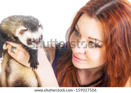Beautiful red haired woman looking at ferret isolated on white background