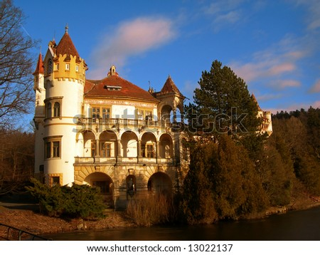 Beautiful romantic castle with river and forest at sunset - stock photo