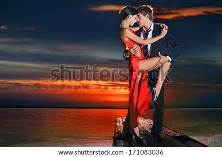 Beautiful romantic couple in tango pose against sunset background. - stock photo