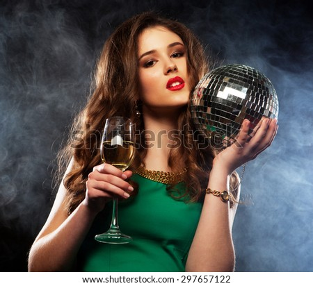 Beautiful sexy woman with a glass of white wine and disco ball - stock photo
