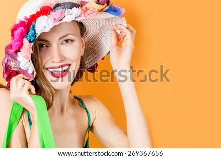 Beautiful shopping woman smiling and wearing a hat over vibrant orange background. Successful and full of fun shopping day concept - stock photo