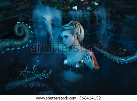 beautiful slim girl in the arms of an octopus, tentacles wrap around the body, fantastic shot, toning fashionable, creative colors - stock photo