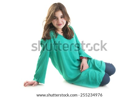 Beautiful teenage girl in green tunic sitting on the floor isolated on white background - stock photo