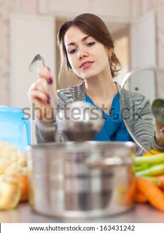 beautiful woman cooking with ladle in  kitchen  at home - stock photo