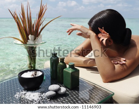 beautiful woman getting spa treatment at daylight near the ocean - stock photo