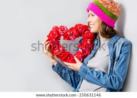 Beautiful woman holding red flower heart over grey background. studio shot