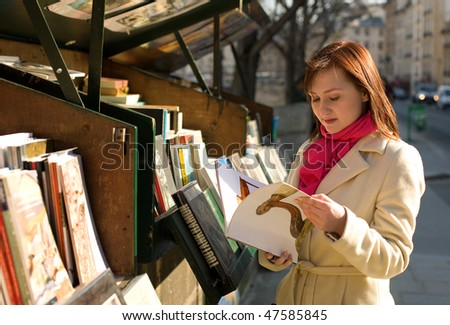 Beautiful woman in Paris selecting a book in an outdoor bookseller box - stock photo