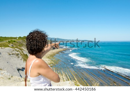beautiful woman, on the background of rocky coast and blue sea