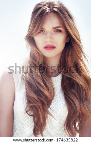 Beautiful woman with long hair  Portrait of beautiful model with long curly hair. Wind blows. Sun is shining. Portrait close up. High fashion model. - stock photo