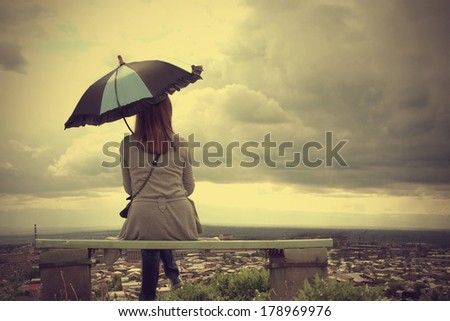 beautiful woman with the umbrella sitting on the  bench - stock photo