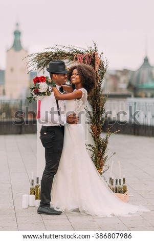 Beautiful young black wedding couple dreamily looks into the sky - stock photo