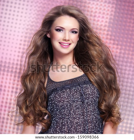 Beautiful  young smiling woman with long hairs looking at camera. Studio portrait.
