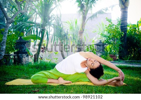 Beautiful young woman doing stretching exercise on green grass at park. Yoga - stock photo