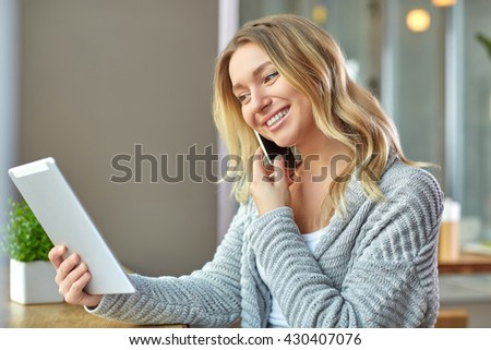 Beautiful young woman holding laptop and talking on the phone at the cafe. Freelancer