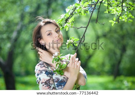 beautiful young woman holds a tree branch - stock photo