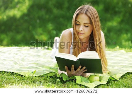 beautiful young woman reading book at park