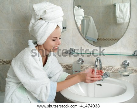 Beautiful young woman washing her face with water