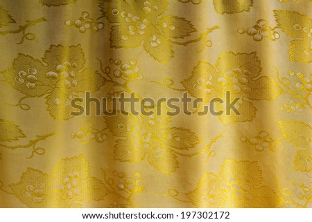 Beautifully draped silk fabric of golden color with an ornament. . It is presented as the background image. - stock photo