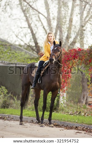 beauty blond hair girl riding a horse in autumn - stock photo